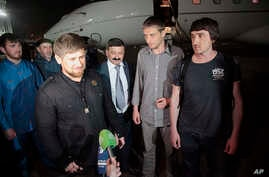 Chechen regional leader Ramzan Kadyrov (l) accompanied by Russian journalists Oleg Sidyakin, second from right, and Marat Saichenko (r) speaks with the press, following their release on late Saturday May 24, from captivity in Ukraine, upon arrival ba