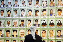 A man looks at photos of Houthi fighters killed during recent armed conflicts, at an exhibition commemorating them in Sana'a, March 5, 2015.