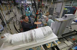 Argonne X-ray scientist Jonathan Almer, left, and Northwestern University Feinberg School of Medicine professor Stuart Stock, right, prepare to use high-energy X-ray beams to learn more about the 1,800-year-old mummified remains in Lemont, Ilinois, N
