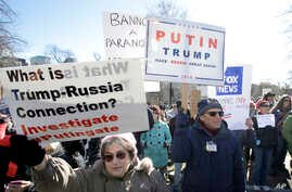 """Protesters hold placards and chant slogans during a demonstration called """"Emergency Rally to Stand for Democracy,"""" Feb. 26, 2017, in Boston."""