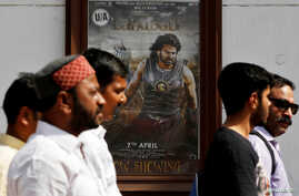 """People walk past a poster of an Indian movie """"Baahubali: The Beginning"""" outside a movie theater in New Delhi, India, April 12, 2017."""