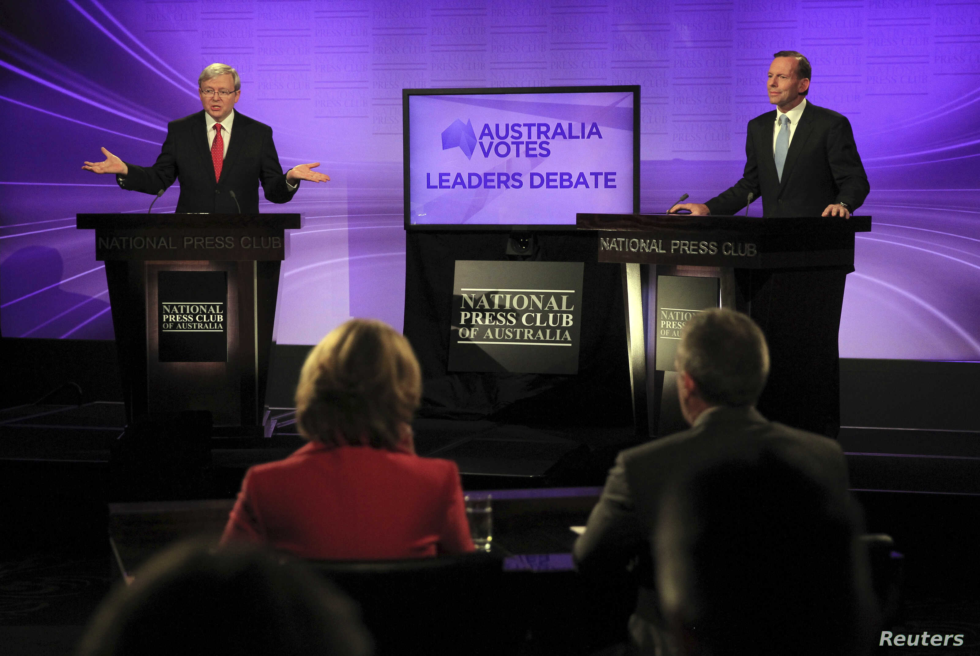 Australian Prime Minister and leader of the Australian Labor Party Kevin Rudd (L) speaks as the leader of the conservative opposition Tony Abbott listens on during their debate at the National Press Club in Canberra, August 11, 2013.