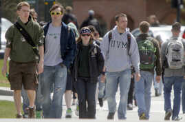 FILE - Students walk across campus at the University of Vermont in Burlington, Vermont.