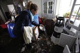 Kerrie Nocella pours seawater out of a bowl from her mother's china set as she helps salvage belongings from her parents' heavily damaged home in the aftermath of superstorm Sandy, Oct. 31, 2012, in Babylon Village, N.Y.