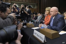 Former Arizona Rep. Gabrielle Giffords, who was seriously injured in the mass shooting that killed six people in Tucson, Arizona two years ago, sits with her husband Mark Kelly on Capitol Hill, Jan. 30, 2013, prior to giving an opening statement befo