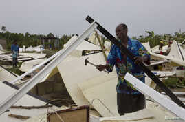 A man works to recover his personal possessions from his flattened home in a camp for displaced people in Port-Au-Prince, Haiti, August 25, 2012.