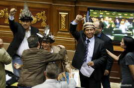 Julio Ygarza, left, Nirma Guarulla, center, and Romel Guzamana, deputies of the Venezuelan coalition of opposition parties, celebrate after their swearing-in ceremony during a session of the National Assembly in Caracas, Jan. 6, 2016.