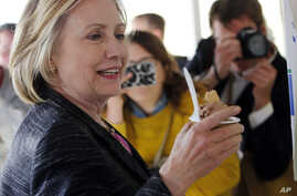 Democratic presidential candidate Hillary Rodham Clinton eyes her chocolate peanut butter fudge ice cream during a stop at Moo's Place, Friday, May 22, 2015, in Derry, N.H.