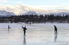 FILE - Ice skaters take advantage of unseasonable warm temperatures to ice skate outside at Westchester Lagoon in Anchorage, Alaska, Jan. 2, 2018. While a large part of the county is freezing under Alaska-like conditions, parts of the nation's northe
