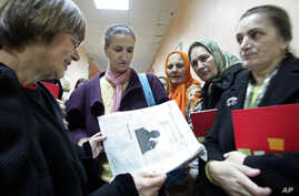 FILE - Human rights activist Natasa Kandic, left, reads a newspaper with family members of slain Bosnian Muslim men and boys at the Special Court building in Belgrade, Serbia, Dec. 21, 2005. The trial of five Serb militiamen charged with executing si