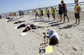 """Amnesty International activists take part in a performance on a beach to commemorate World Refugee Day in Valencia, Spain, June 20, 2015. The sign, right, reads, """"I flee from gender violence."""""""