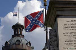 The U.S. flag and South Carolina state flag flies at half staff to honor the nine people killed in the Charleston murders as the confederate battle flag also flies on the grounds of the South Carolina State House in Columbia, SC, June 20, 2015.