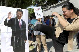 An activist kicks a portrait of Chinese President Xi Jinping during a protest against the upcoming meeting  between Taiwan's President Ma Ying-jeou and Chinese President Xi Jinping, in front of the Presidential Office in Taipei, Taiwan, November 5, 2