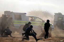 Policemen in teargas and dust open fire on striking miners at the Lonmin Platinum Mine near Rustenburg, South Africa, August 16, 2012.