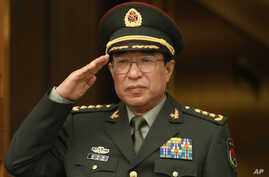 FILE - Chinese General Xu Caihou listens to national anthems during welcome ceremony at the Pentagon, Washington.