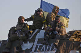 Ukrainian troops ride on an armored vehicle outside Artemivsk, Ukraine, while pulling out of Debaltseve, Wednesday, Feb. 18, 2015.