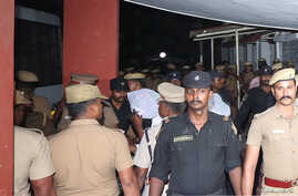 Police escort one of the men (face covered) accused of raping a 12-year girl inside the high court premises in Chennai, India, July 17, 2018.