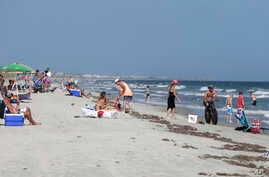 FILE - Vacationers relax on the bench and in the surf in Oak Island, N.C. — an area where two shark attacks have occurred in the last two weeks.