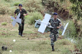 Lebanese Army soldiers carry parts of an Israeli drone in the Marjeyoun countryside, south Lebanon Sept. 20, 2014. The MK drone fell in the Marjeyoun countryside near the Lebanese-Israeli border, the National News Agency (NNA) reported. The Israel De