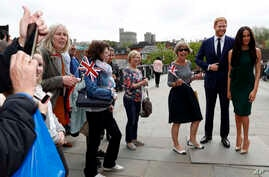 Tourists gather to take photos with waxwork figures of Britain's Prince Harry and Meghan Markle against the backdrop of Windsor Castle, in Windsor, England, May 16, 2018.