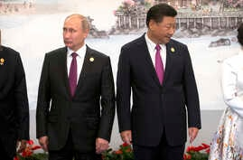 Russian President Vladimir Putin, left, and Chinese President Xi Jinping line up for a photo during the BRICS Summit in southeastern China's Fujian province, Sept. 4, 2017.