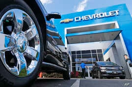 This April 26, 2017 photo shows the logo on the wheel of an SUV in front of a Chevrolet dealership in Richmond, Va. General Motors and Ford each posted strong U.S. sales in Sept. 2017, confirming predictions that the industry could rebound for the mo