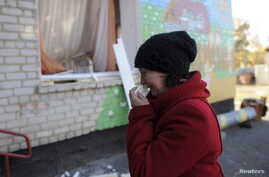 FILE - A woman cries outside a local kindergarten, which was damaged by explosions at a military depot in Svatove, Luhansk region, Ukraine, Oct. 30, 2015.
