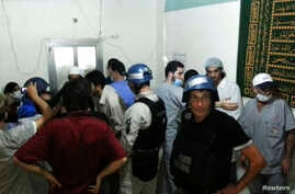 U.N. chemical weapons experts visit a hospital where wounded people affected by a suspected gas attack are being treated, in the southwestern Damascus suburb of Mouadamiya, Aug. 26, 2013.