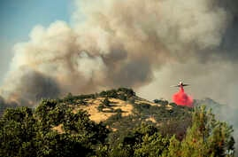 An air tanker drops retardant on a wildfire above the Spring Lakes community, June 24, 2018., near Clearlake Oaks, California.