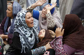 Relatives and families of members of Muslim Brotherhood and supporters of ousted President Mohamed Mursi react after hearing the sentence, in front of the court in Minya, south of Cairo, Apr. 28, 2014.