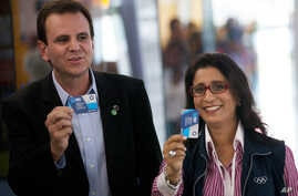 Nawal El Moutawakel, head of the IOC Evaluation Commission, right, and Eduardo Paes, Rio de Janeiro's Mayor, show tickets before boarding a Bus Rapid Transit (BRT) during the 3rd visit of the IOC Coordination Commission for the Rio Olympics 2016 in R