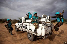 In this photo released by the United Nations African Union Mission in Darfur (UNAMID), Tanzanian UNAMID troops patrol Khor Abeche, South Darfur, Sudan.