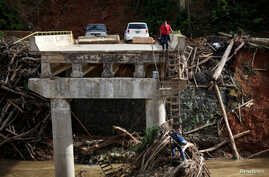 A woman looks as her husband climbs down a ladder at a partially destroyed bridge, after Hurricane Maria hit the area in September, in Utuado, Puerto Rico, Nov. 9, 2017.
