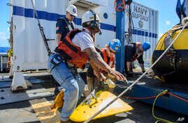 Contractors and Lt. Cmdr. Daniel Neverosky retrieve and secure the tow pinger locator aboard the USNS Apache, which left Norfolk, Va., on Oct. 19, to begin searching for wreckage from the missing cargo ship El Faro, Oct. 24, 2015.