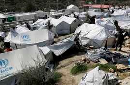 FILE - A regugee is seen walking at the Moria refugee camp on the northeastern Greek island of Lesbos, March 16, 2017. Overcrowding has been affecting the physical and mental health of the local refugee population, U.N. officials say.