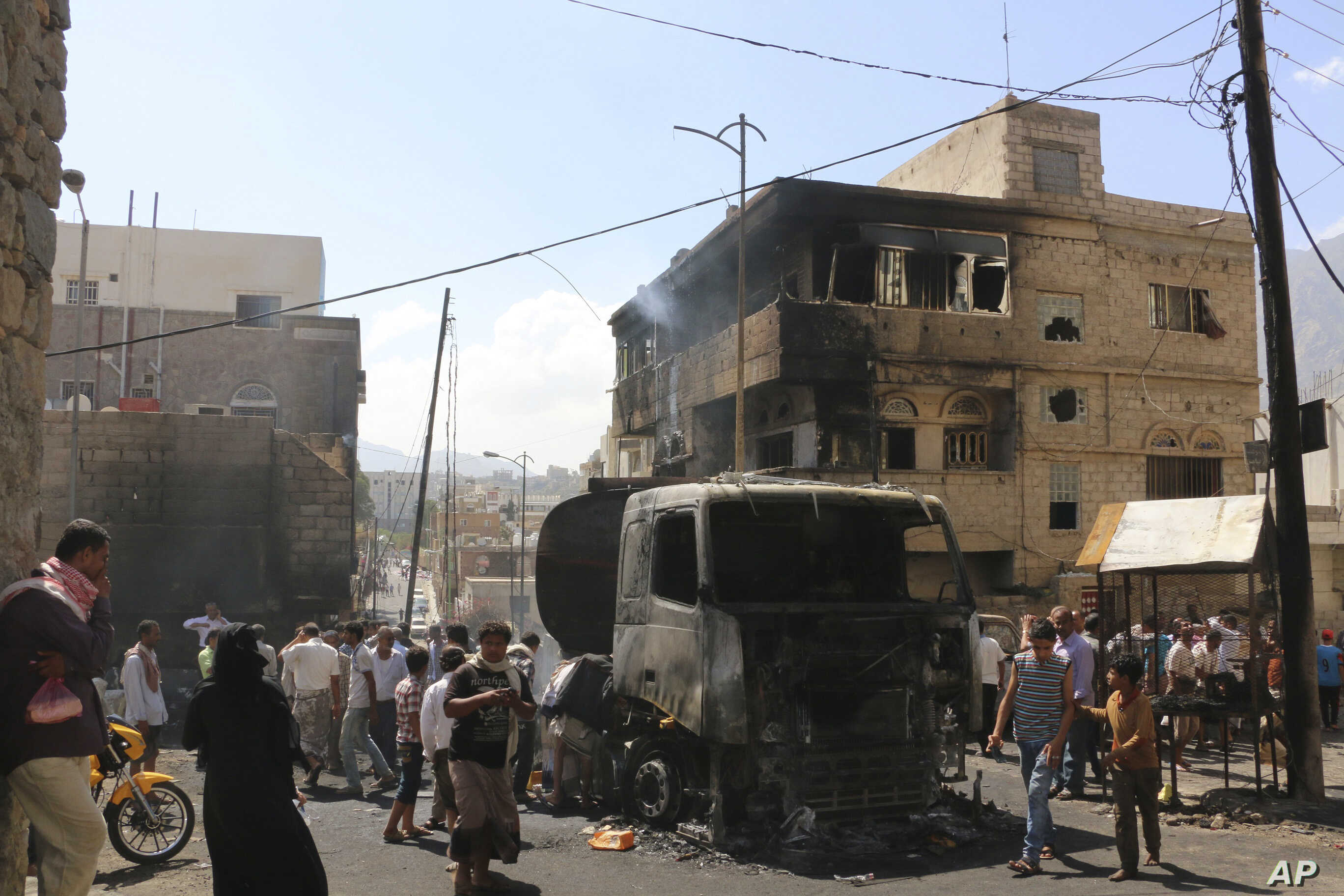 People gather around a truck carrying oil that was hit by crossfire between fighters loyal to the exiled President Abed Rabbo Mansour Hadi and Shi'ite rebels in Taiz city, Yemen, May 25, 2015.