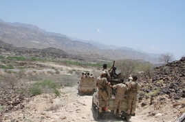 In this May 1, 2014 photo provided by Yemen's Defense Ministry, army vehicles patrol a road during fighting with al-Qaida militants in Majala of the southern province of Abyan, Yemen.
