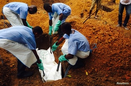 Volunteers lower a corpse, which is prepared with safe burial practices to ensure it does not pose a health risk to others and stop the chain of person-to-person transmission of Ebola, into a grave in Kailahun August 2, 2014. Hundreds of troops were