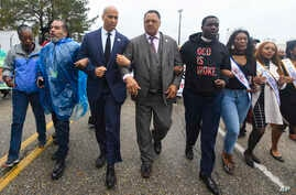 U.S. Sen. Cory Booker, D-N.J., third from left, and the Rev. Jesse Jackson march to cross the Edmund Pettus Bridge Sunday, March 3, 2019, during the Bloody Sunday commemoration in Selma, Alabama.