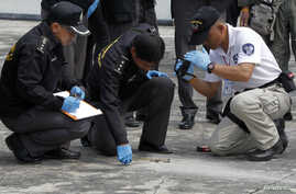FILE - Members of the police bomb squad investigate the site of a grenade attack on a roof of the National Anti-Corruption Commission office in Nonthaburi province, on the outskirts of Bangkok, March 25, 2014.