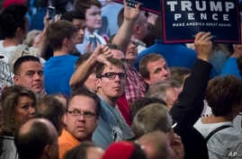 Supporters of Republican presidential candidate Donald Trump react toward reporters and photographers during a campaign rally in Cincinnati, Oct. 13, 2016.