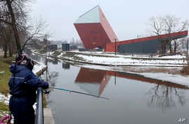 FILE - In this photo taken in Gdansk, Poland, Jan. 23, 2017, a woman fishes near the Museum of the Second World War, an ambitious new museum under creation for nine years. It opened to visitors, March 23, 2017.