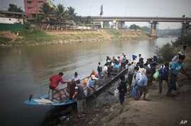 Burmese migrants, illegal workers use boat to cross Moei River bordering town of Myawaddy, Burma, visible in the background, to Mae Sot, Thailand, March 21, 2012.