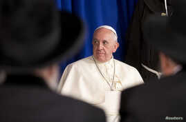 Pope Francis listens to a speech as he meets Israel's Rabies David Lau and Yitzhak Yosef in Jerusalem, May 26, 2014.