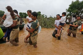 India army soldiers carry children rescued from flood affected villages near Thara in Banaskantha district, Gujarat, India, Wednesday, July 26, 2017.