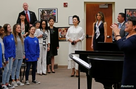 U.S. first lady Melania Trump and China's first lady Peng Liyuan listen as students perform for them during a visit to Bak Middle School of the Arts in West Palm Beach, Florida, April 7, 2017.