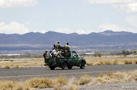 Houthi militants travel on a vehicle on the runway of the international airport of Yemen's capital Sanaa,  May 5, 2015.