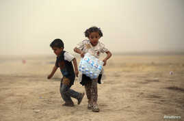 A girl, who fled from the violence in Mosul, carries a case of water at a camp on the outskirts of Arbil in Iraq's Kurdistan region, June 12, 2014.
