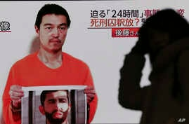 A passerby is silhouetted against a large TV broadcasting a news program showing a still photo of Japanese hostage Kenji Goto holding what appears to be a photo of Jordanian pilot Mu'ath al-Kaseasbeh, in Tokyo, Jan. 28, 2015.