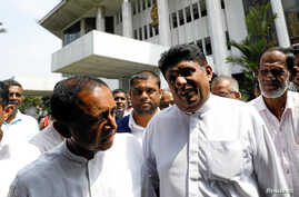 Sajith Premadasa (2nd R) deputy leader and Kabir Hashim (L) senior member of the deposed Prime Minister Ranil Wickremesingehe-led United National Party talk as they leave the Supreme Court after filing a petition against the President Maithripala Sir